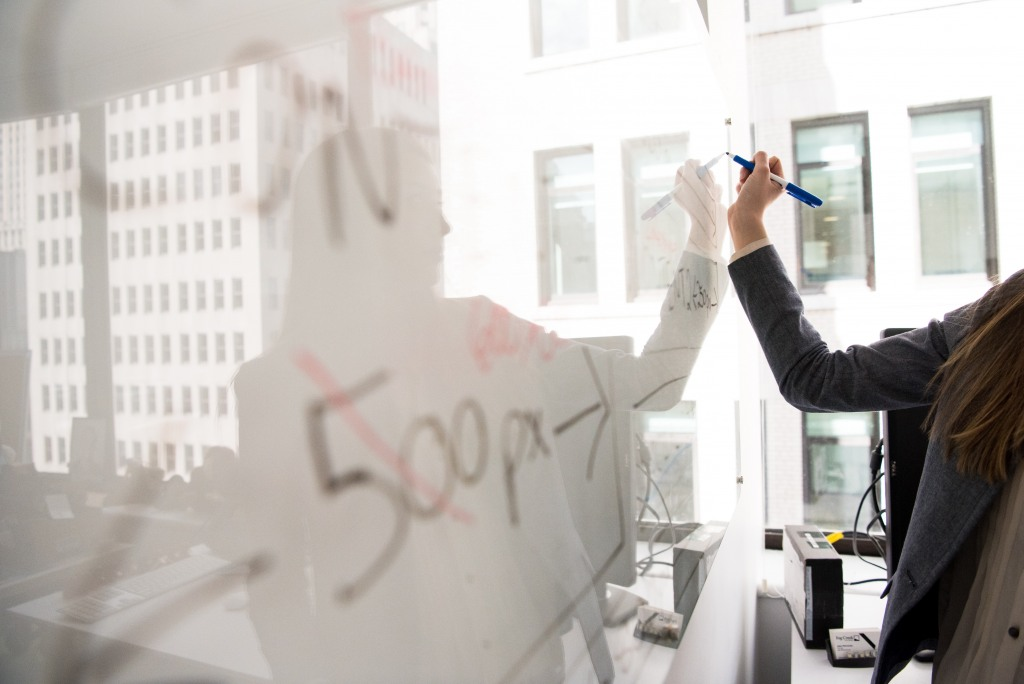 Woman writing on whiteboard priorities, benefits of IT outsourcing
